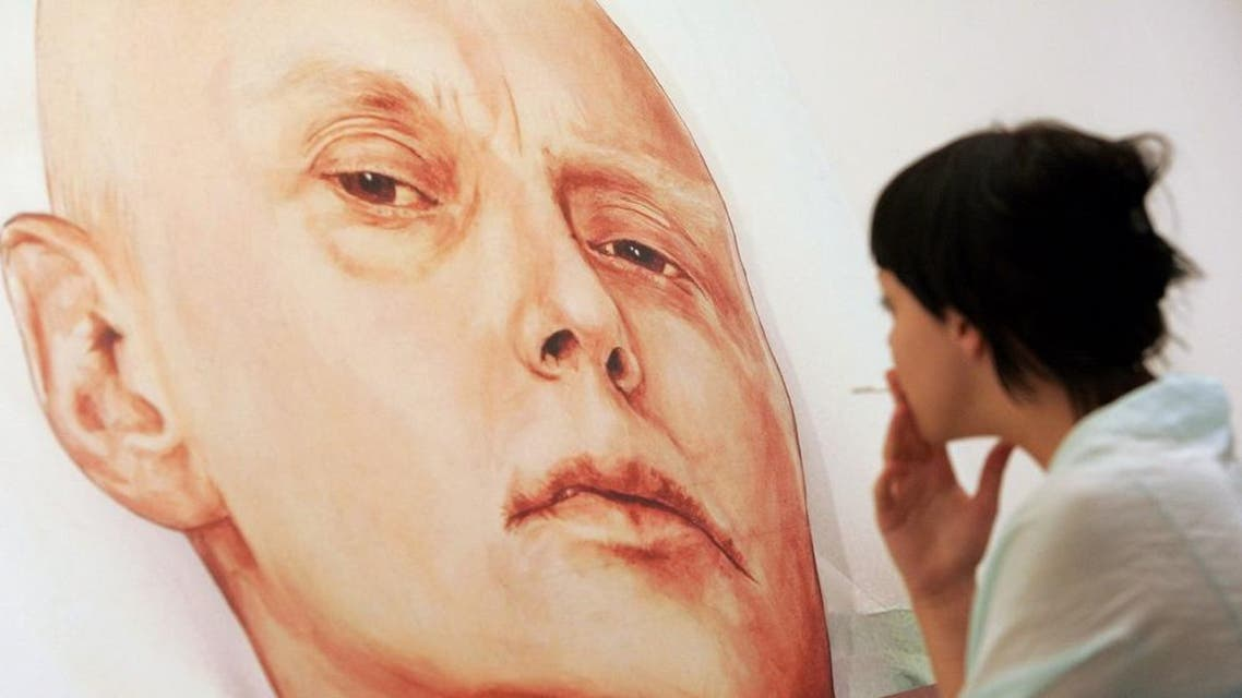 """A file photo taken on May 23, 2007, shows a visitor as she looks at a painting showing former Russian spy Alexander Litvinenko in his hosital bed in London, by painters Dmitry Vrubel and Viktoria Timofeyeva, in the Marat Guelman gallery in Moscow. Russian President Vladimir Putin """"probably approved"""" the killing of ex-spy Alexander Litvinenko in London, a British inquiry into his agonising death by radiation poisoning found on January 21, 2016. AFP PHOTO / NATALIA KOLESNIKOVA"""