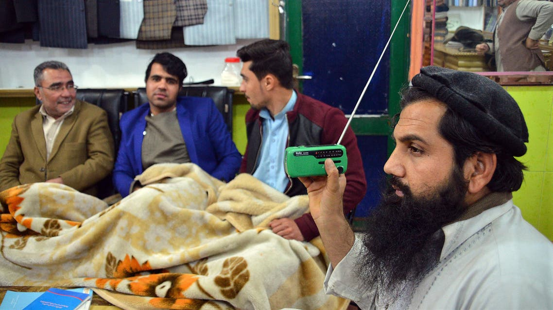 In this photo taken on Sunday, Jan. 10, 2016, an Afghan shopkeeper, right, listens to Islamic State Radio at his shop in Jalalabad, capital of Nangarhar province, Afghanistan. AP