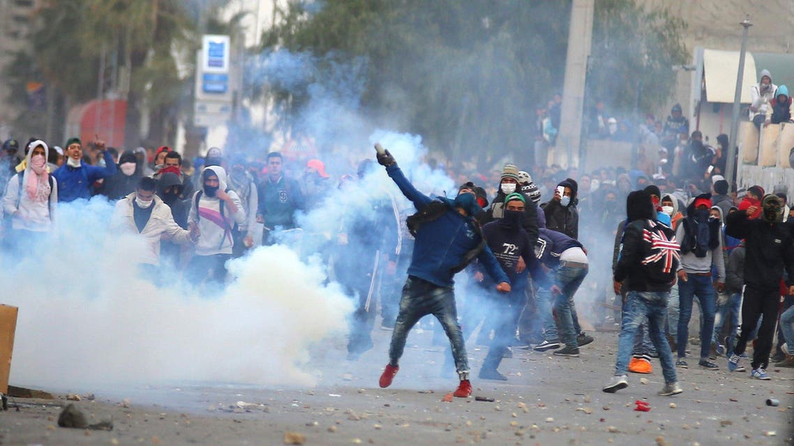 A protester throws a tear gas canister back toward police during a protest outside the local government office in Kasserine, Tunisia January 21, 2016. (Reuters)