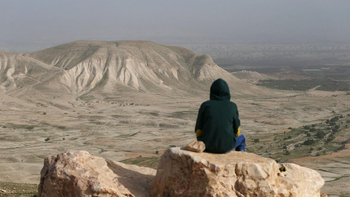 A Palestinian man sits on a rock at Jordan Valley near the West Bank city of Jericho. (Reuters)