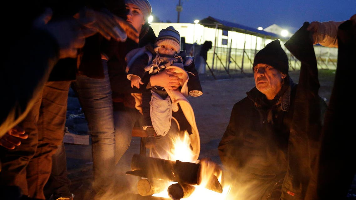 Refugees try to warm up around a fire at a refugee camp in the northern Greek village of Idomeni Thursday, Jan. 21, 2016. (AP)