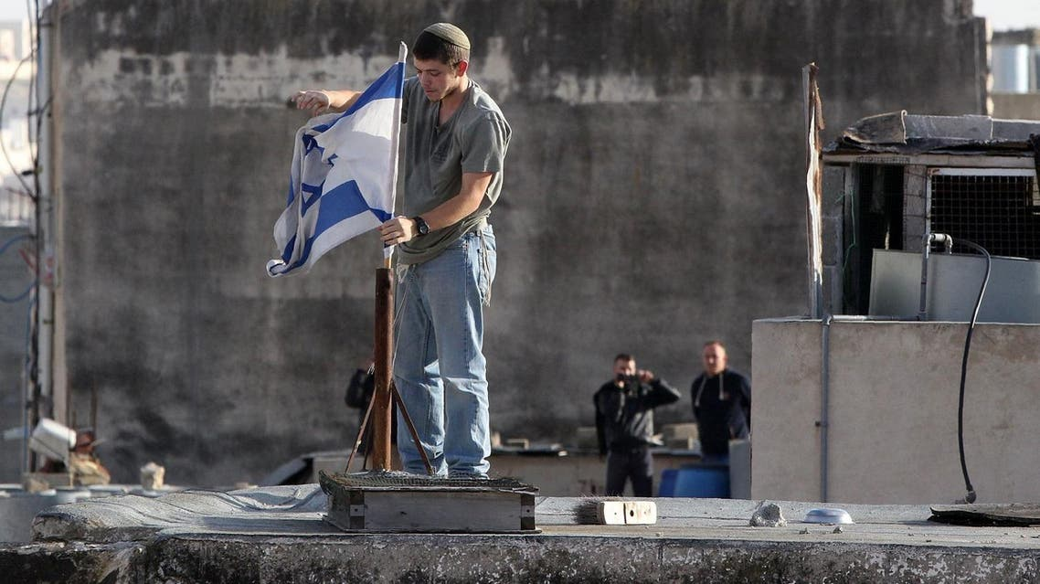 An Israeli settler fixes an Israeli flag on the roof of a building after dozens of settlers entered two homes in a building in the centre of the Palestinian city Hebron. (AFP)