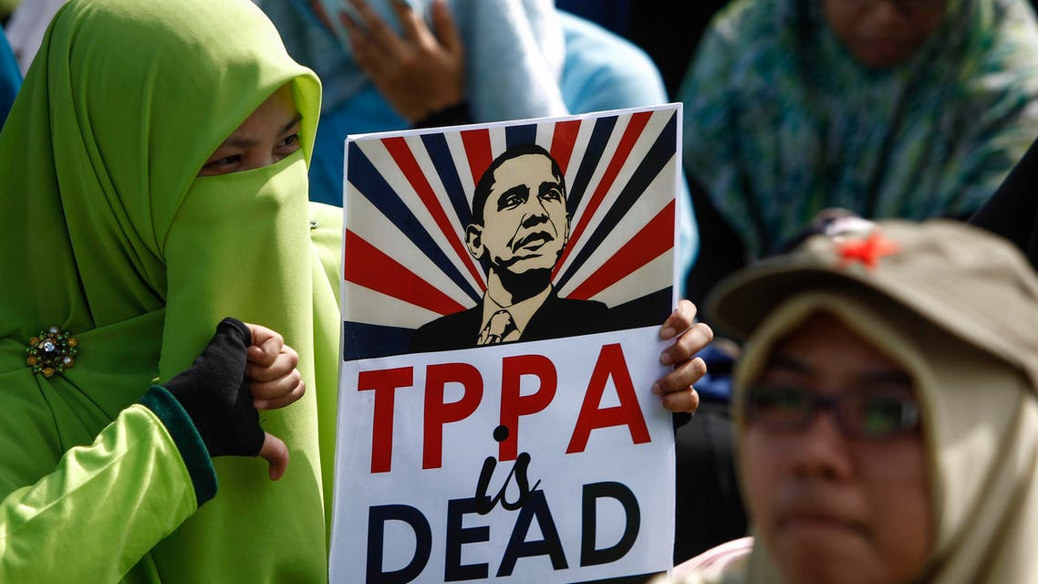 A Malaysian Muslim woman protestor poses for photograph holding an anti-TPPA (Trans-Pacific Partnership Agreement) placard with U.S. President Barack Obama's caricature during a protest in Kuala Lumpur, Malaysia, Saturday, Jan. 23, 2016. The Malaysian parliament is to hold a special sitting next week to debate on whether Malaysia should join the TPPA. (AP Photo/Joshua Paul)