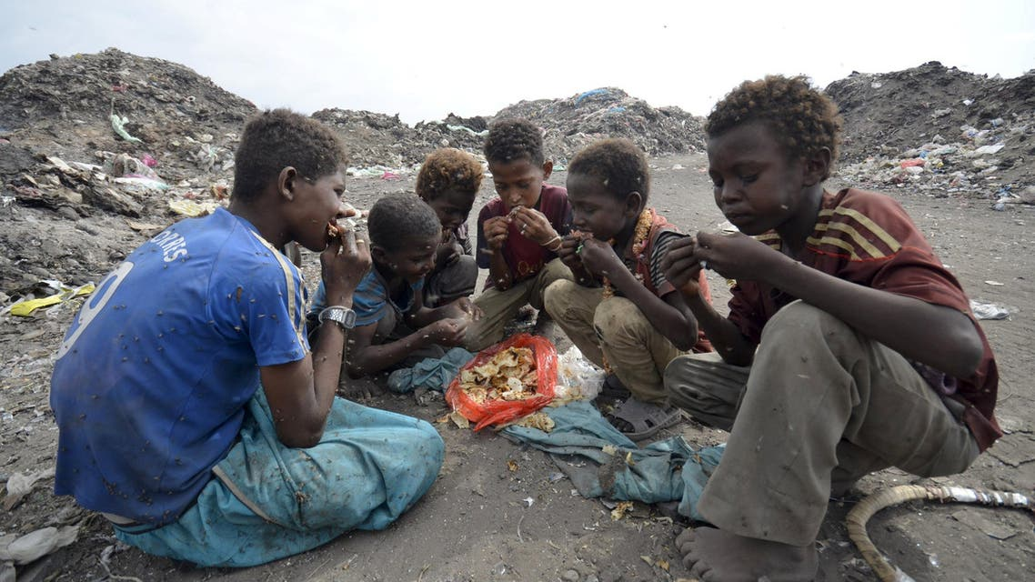Boys eat at a rubbish dump where they are collecting recyclable waste outside Yemen's Red Sea port city of Houdieda January 20, 2016. REUTERS/Abduljabbar Zeyad TPX IMAGES OF THE DAY