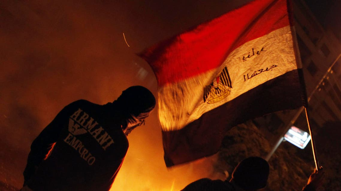 A protester, who opposes Egyptian President Mohamed Mursi, waves the national flag at riot police during clashes in front of the presidential palace in Cairo February 8, 2013. (Reuters)