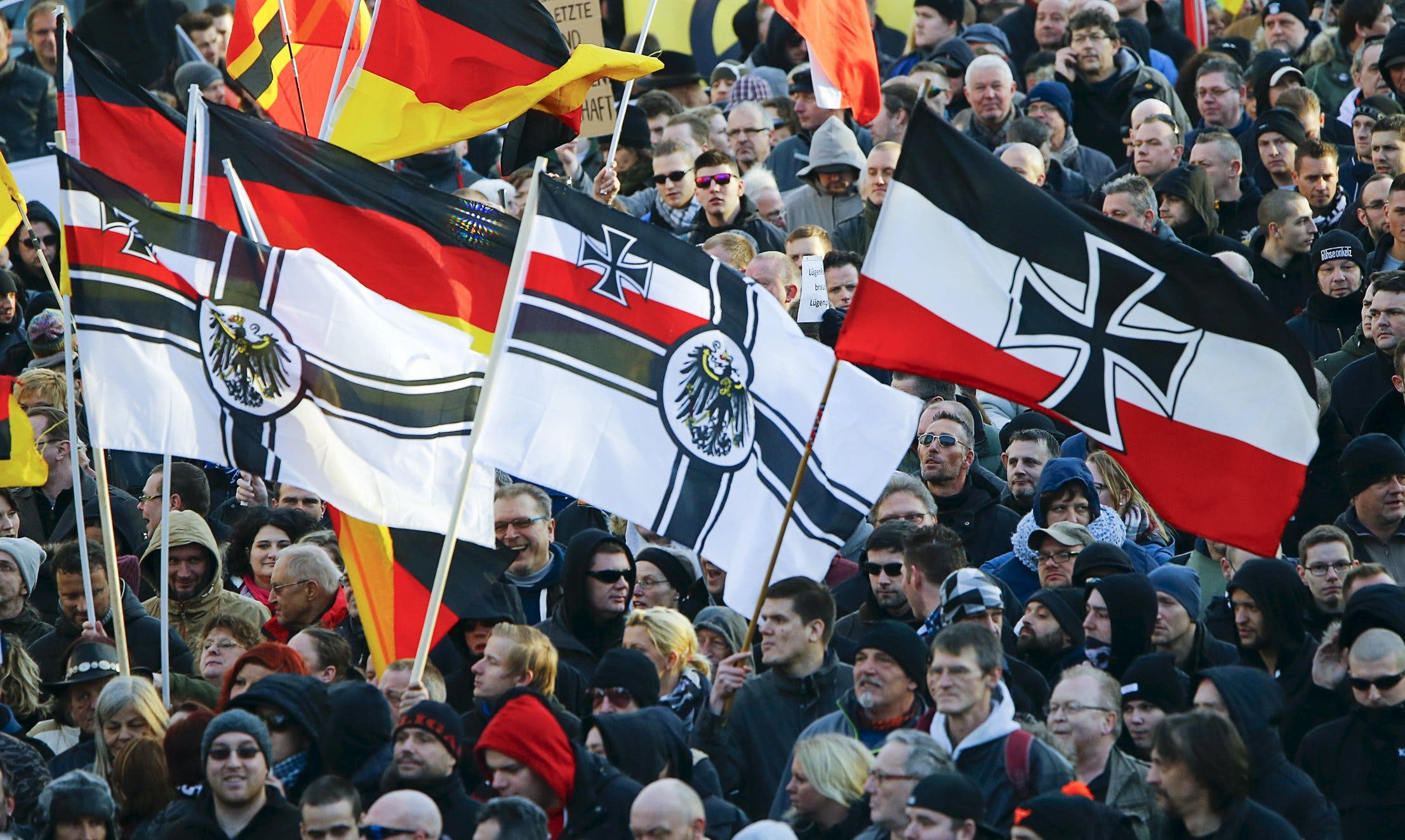 Supporters of anti-immigration right-wing movement PEGIDA (Patriotic Europeans Against the Islamisation of the West) carry various versions of the Imperial War Flag (Reichskriegsflagge) during a demonstration march, in reaction to mass assaults on women on New Year's Eve, in Cologne, Germany January 9, 2016. reuters