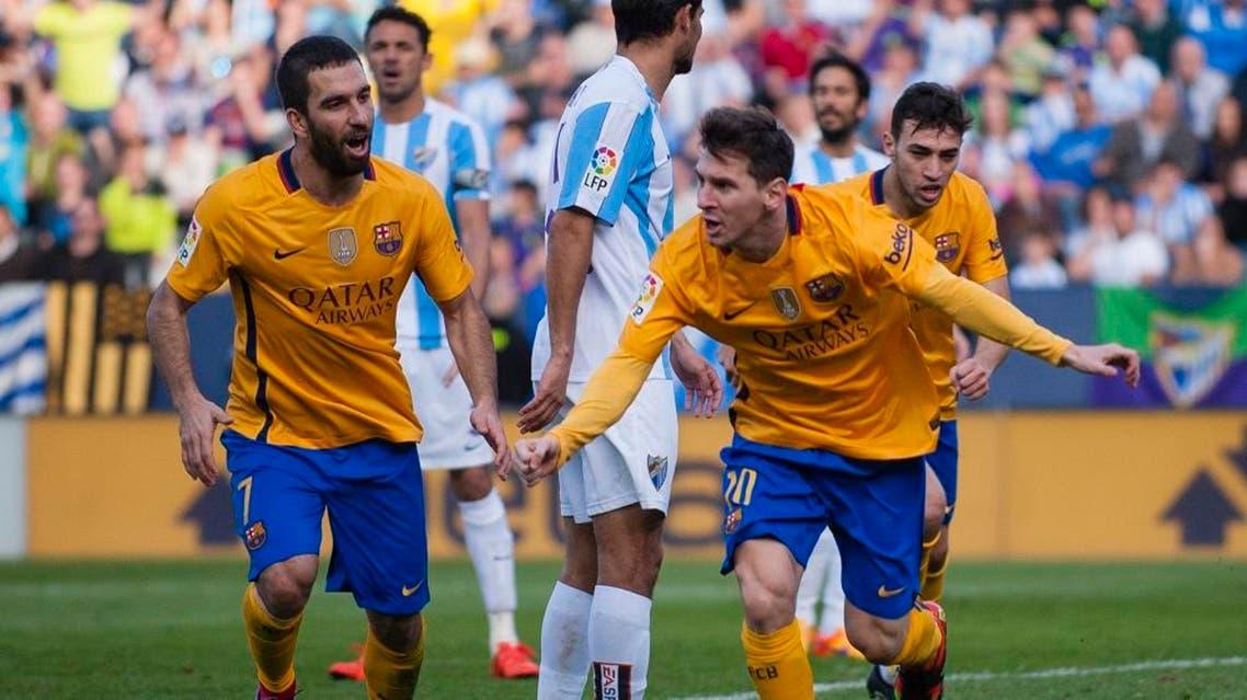FC Barcelona's Lionel Messi, right, reacts next to teammate Arda Turan after scoring against Malaga during a Spanish La Liga soccer match between Malaga and FC Barcelona at La Rosaleda stadium in Malaga, Spain, Saturday, Jan. 23, 2016 (AP)
