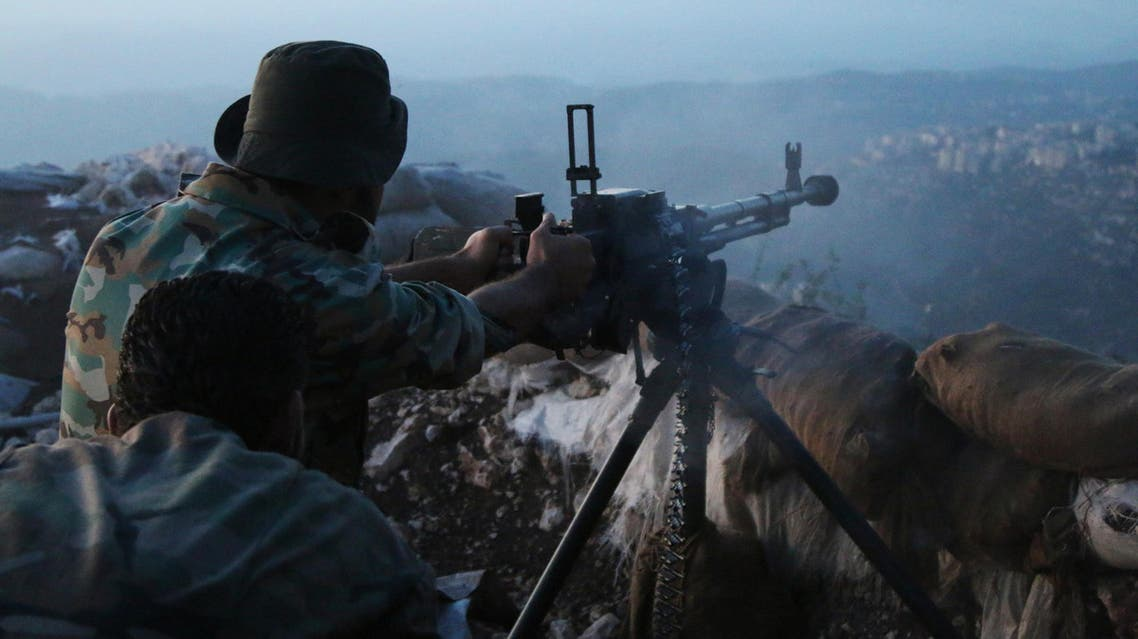 In this photo taken on Saturday, Oct. 10, 2015, Syrian army personnel fire a machine gun in Latakia province, about 12 miles from the border with Turkey, Syria. Backed by Russian airstrikes, the Syrian army has launched an offensive in central and northwestern regions. AP