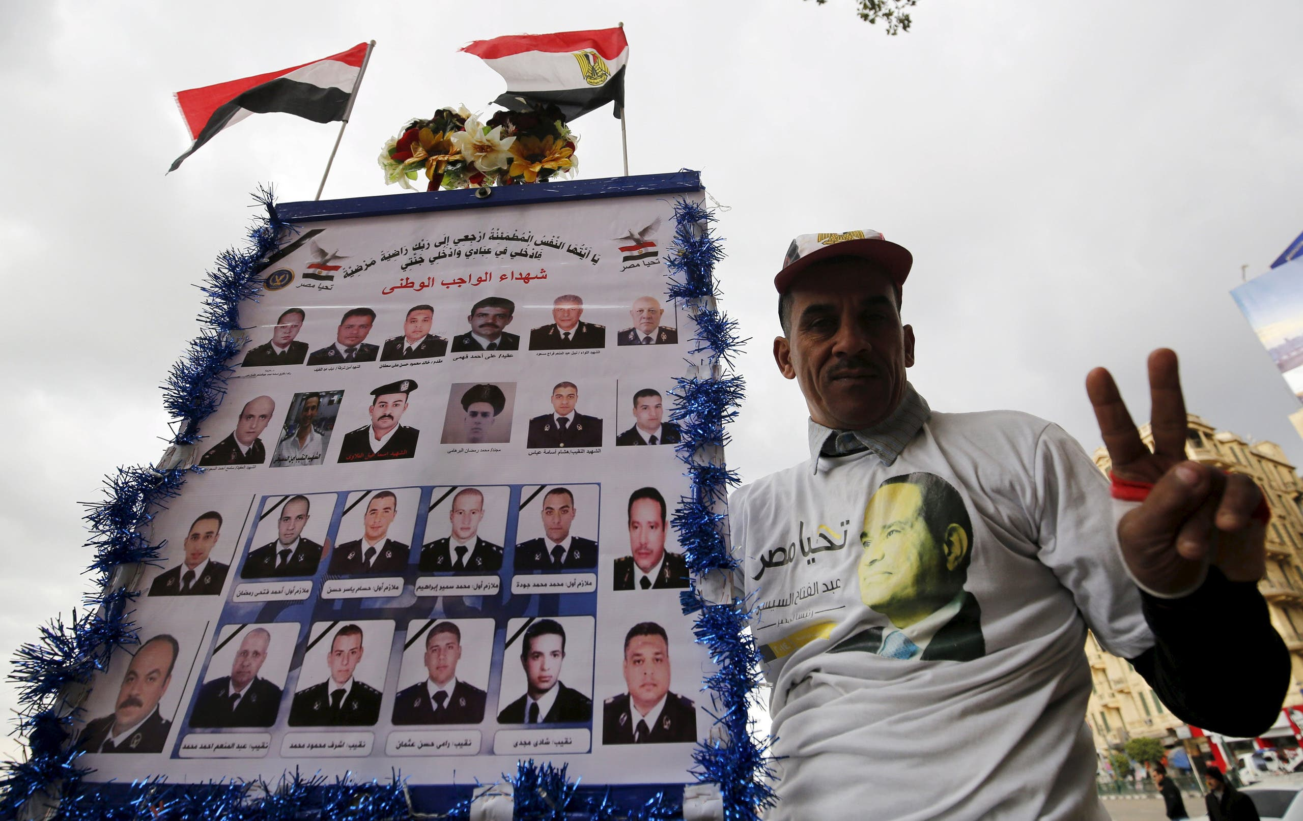 A pro-government protester chants slogans while holding a poster with pictures of martyrs police and army during the fifth anniversary of the uprising that ended the 30-year reign of Hosni Mubarak in Cairo, Egypt, January 25, 2016. REU