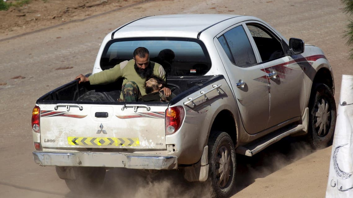 An injured Ahrar al-Sham Islamic Movement rebel fighter rides on the back of a pick-up truck with a fellow fighter in the northwestern city of Idlib March 26, 2015. (Reuters)