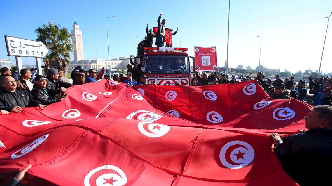 Tunisian police officers and security personnel shout slogans and hold flags during a protest in Tunis. (Reuters)