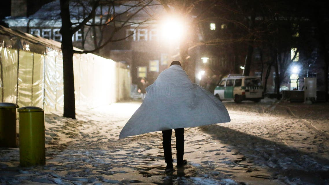 A man covered with blanket against the cold arrives at the central registration center for refugees and asylum seekers, LaGeSo (Landesamt fuer Gesundheit und Soziales - State Office for Health and Social Affairs) in Berlin, Wednesday, Jan. 6, 2016. German Interior Minister will present a migration report on Wednesday. (AP Photo/Markus Schreiber)