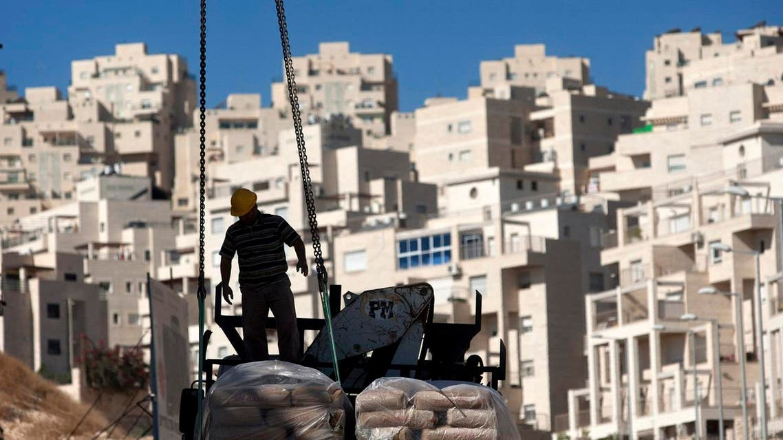 A worker stands by construction materials to unload at a new housing unit in the east Jerusalem neighborhood of Har Homa. (File photo: AP)
