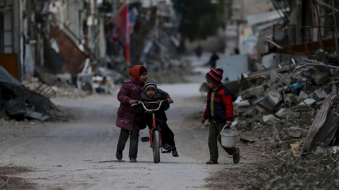 A girl pushes a boy on a bicycle past damaged buildings in Jobar, a suburb of Damascus, Syria January 23, 2016. (Reuters)
