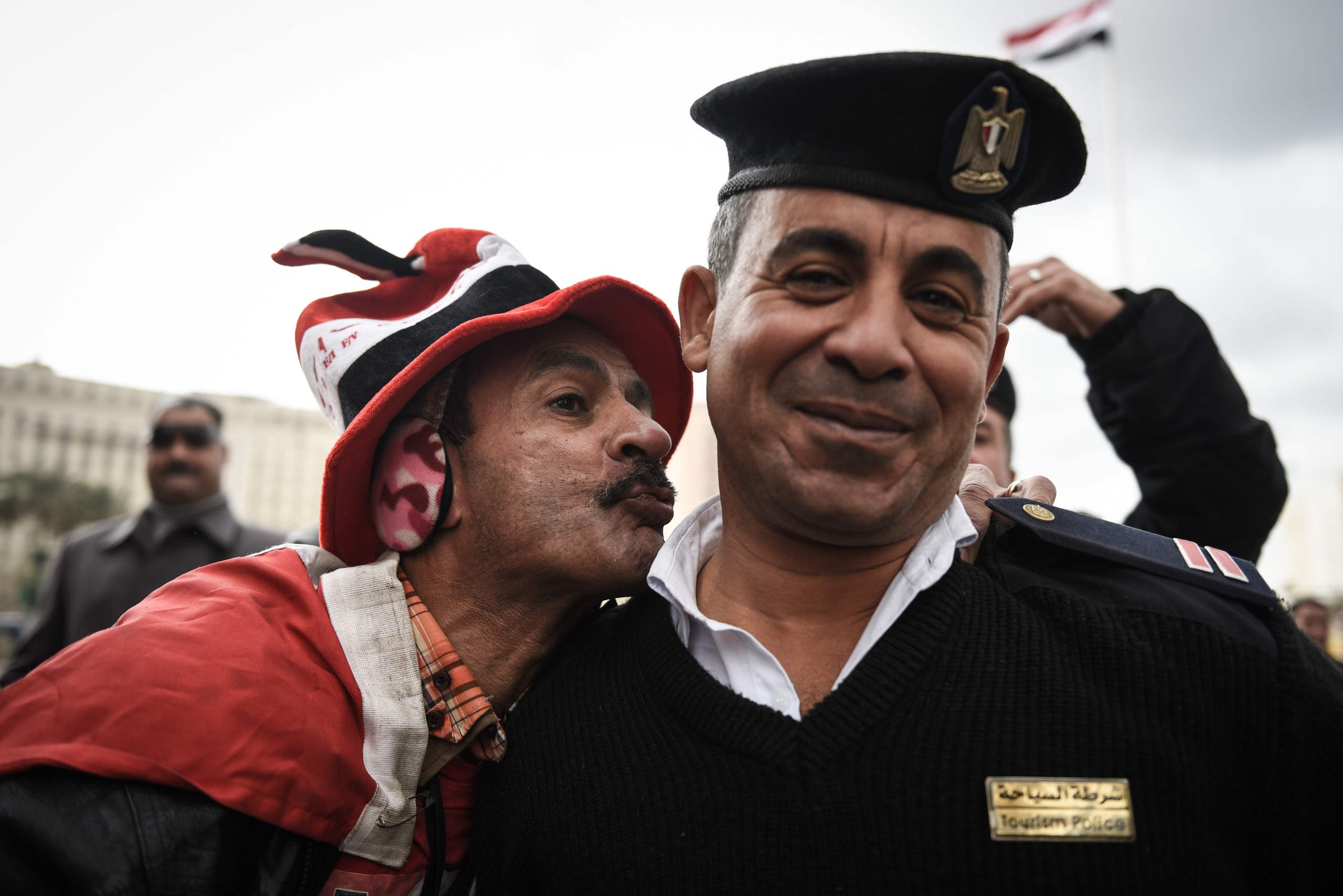 A pro-government Egyptian man kisses a policeman on Cairo's landmark Tahrir Square on January 25, 2016, as the country marks the fifth anniversary of the 2011 uprising. AFP