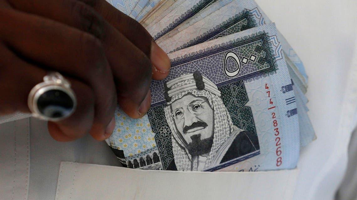 A Saudi man shows Saudi riyal banknotes at a money exchange shop, in Riyadh, Saudi Arabia January 20, 2016. (Reuters)