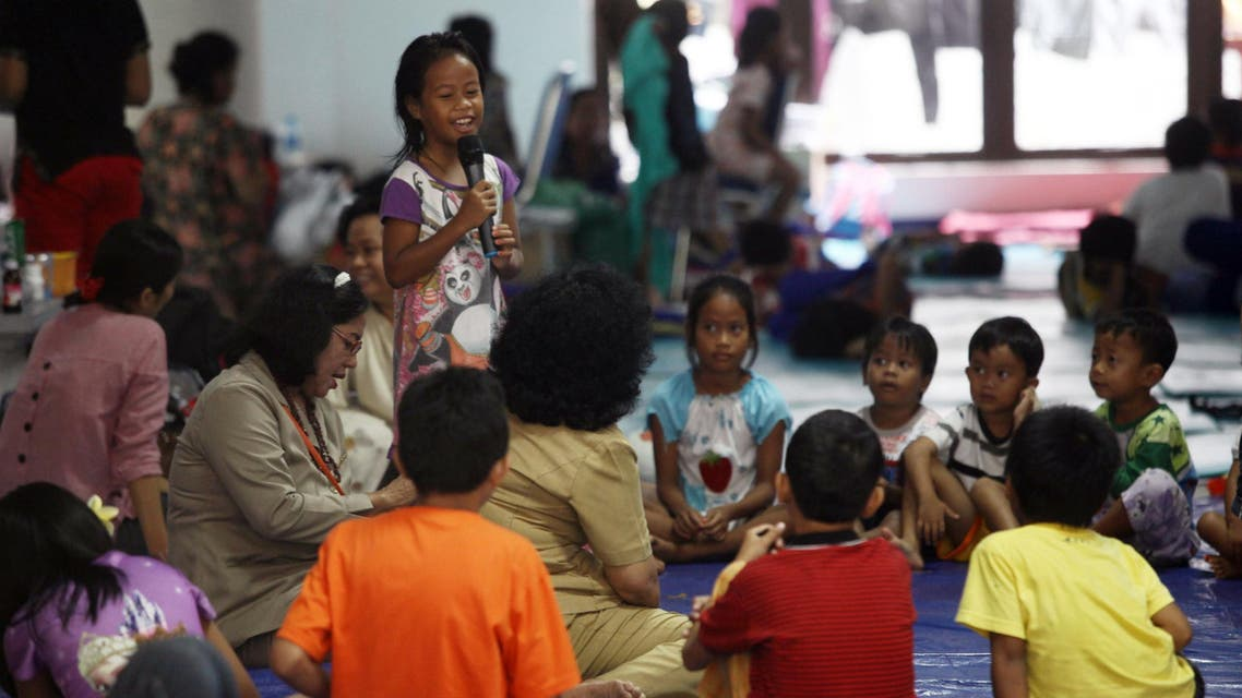 """BAY1755 - JAKARTA, -, INDONESIA : In this photo taken on January 26, 2016, children of members of the Light of Nusantara Movement (Gafatar), who were relocated from their village in Borneo following a mob attack, play and learn at a shelter in Jakarta. Indonesia has relocated more than 1,500 members of a controversial sect from their village """"for their own safety"""", an official said January 27, but rights groups described their treatment as religious persecution. AFP PHOTO / Muhammad RASYA"""