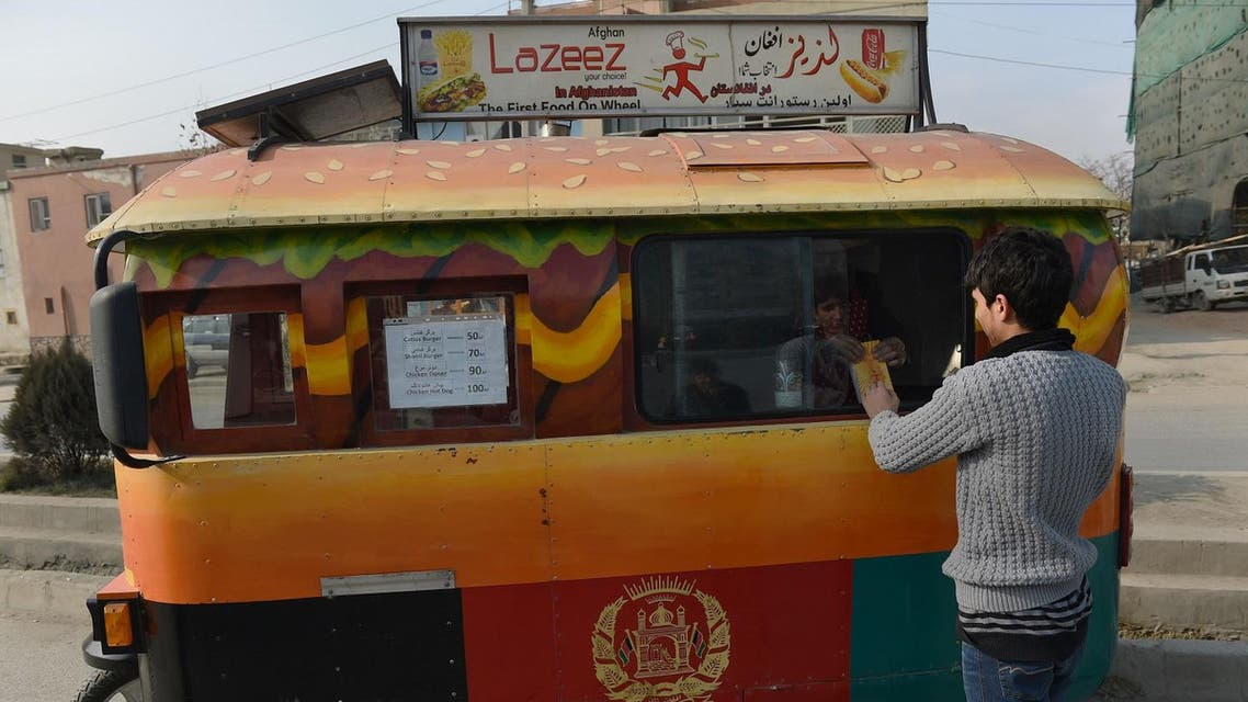 an Afghan customer buys a burger from a Lazeez food truck in Kabul. (AFP)