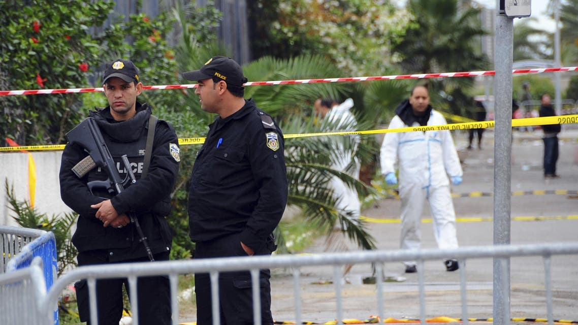 Police officers secure the area where a bus exploded Tuesday in Tunis, Wednesday Nov.25, 2015. Tunisia's Interior Ministry says 10 kilograms (22 pounds) of military explosives were used in an attack on a bus carrying presidential guards that left at least 13 people dead. (AP Photo)