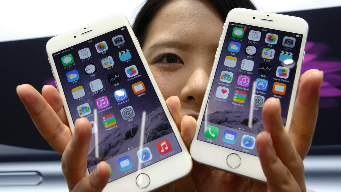 a customer shows off the new Apple iPhone 6, right, and 6 Plus at a store in Tokyo. AP
