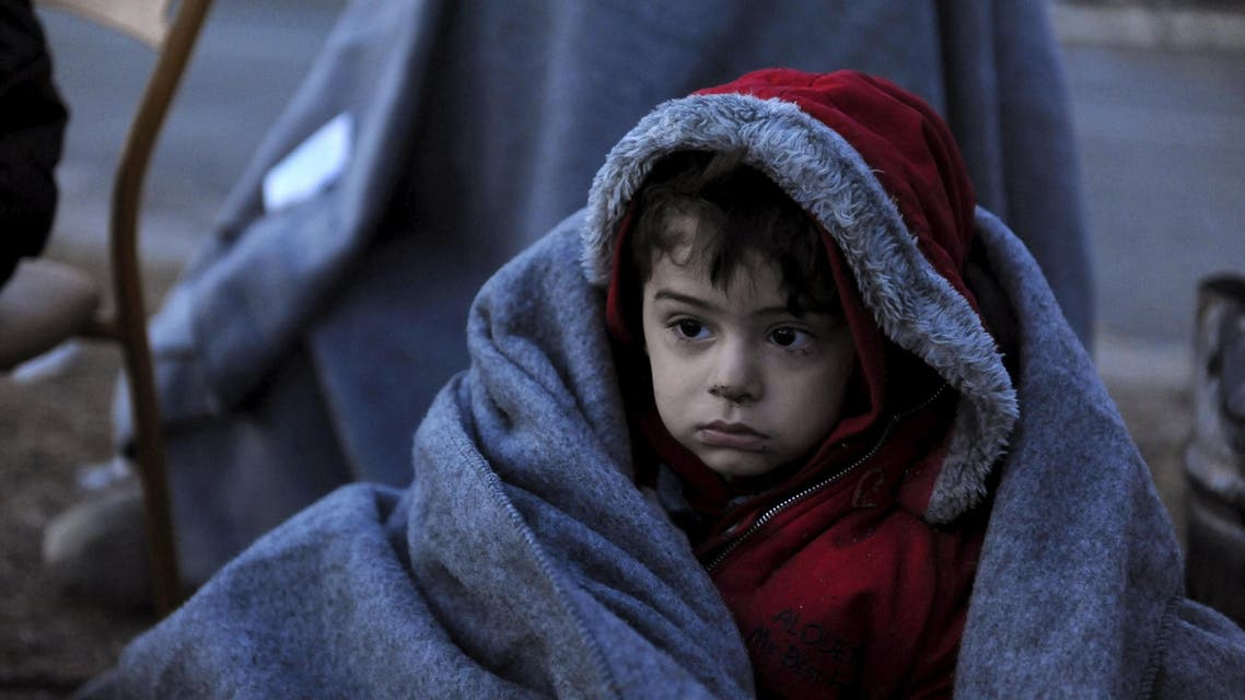 A migrant boy is covered with a blanket as he and other refugees and migrants wait to cross the Greek-Macedonian border near the village of Idomeni, Greece, January 28, 2016. REUTERS/Alexandros Avramidis GREECE OUT. NO COMMERCIAL OR EDITORIAL SALES IN GREECE