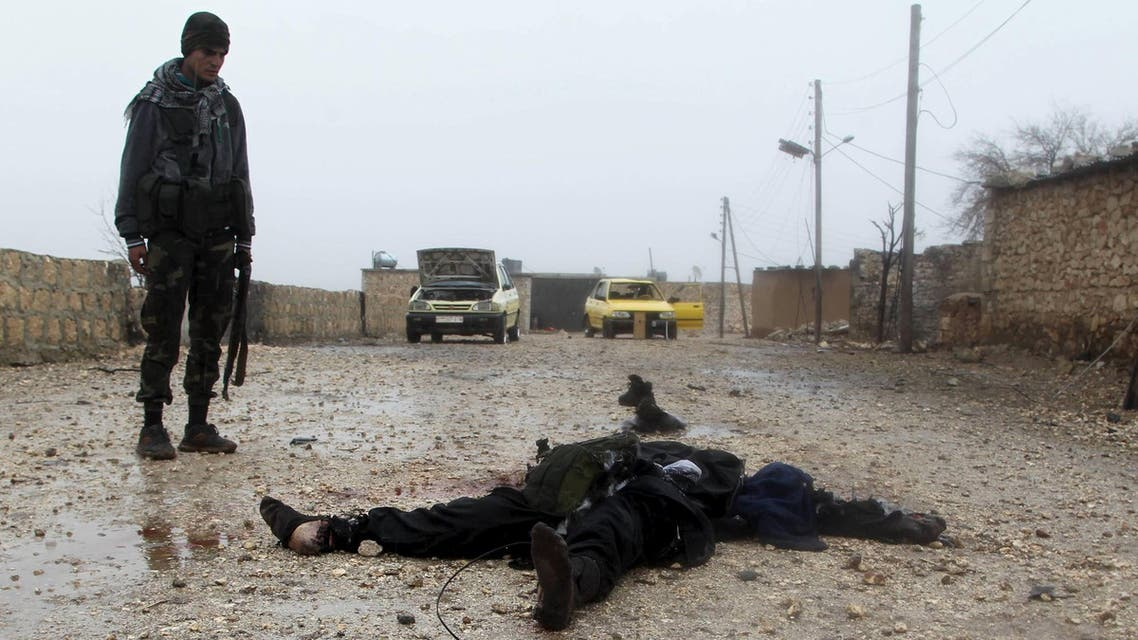 Free Syrian Army fighter inspects a dead Islamic State fighter after they took control of the area in the northern Aleppo countryside, Syria, January 18, 2016. (Reuters)