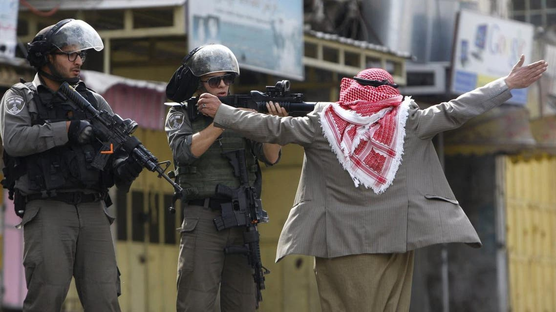 An old Palestinian man prevents an Israeli border policeman from shooting at protesters during clashes in the West Bank city of Hebron October 10, 2015. (Reuters)