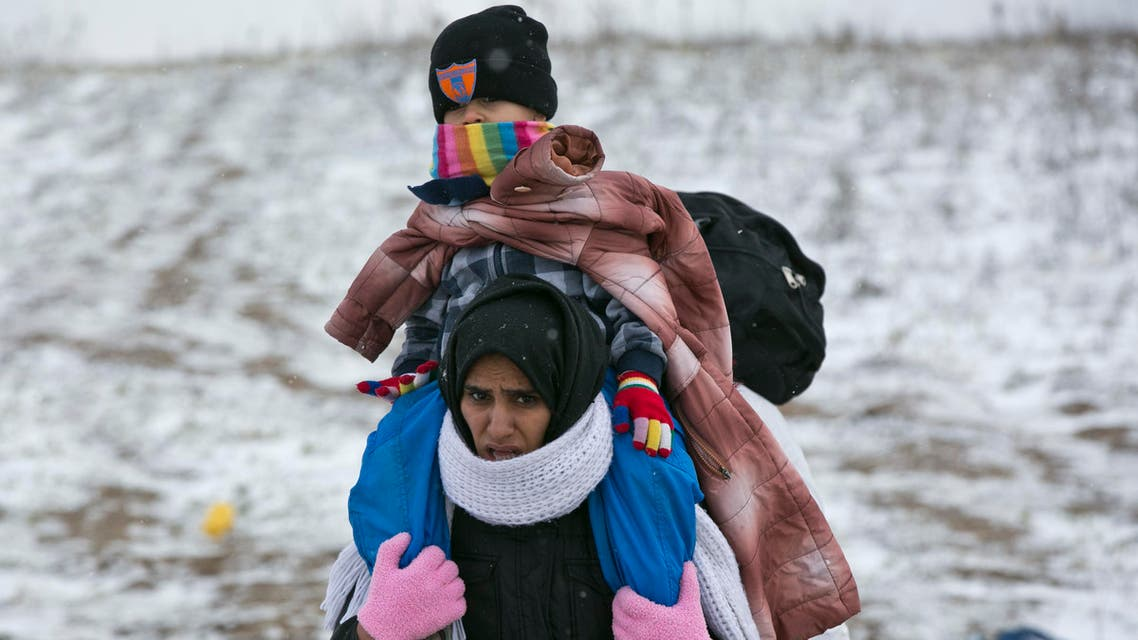 A migrant mother carries her child as they walk through snow, from the Macedonian border into Serbia, near the village of Miratovac, Serbia, Monday, Jan. 18, 2016.  (AP)