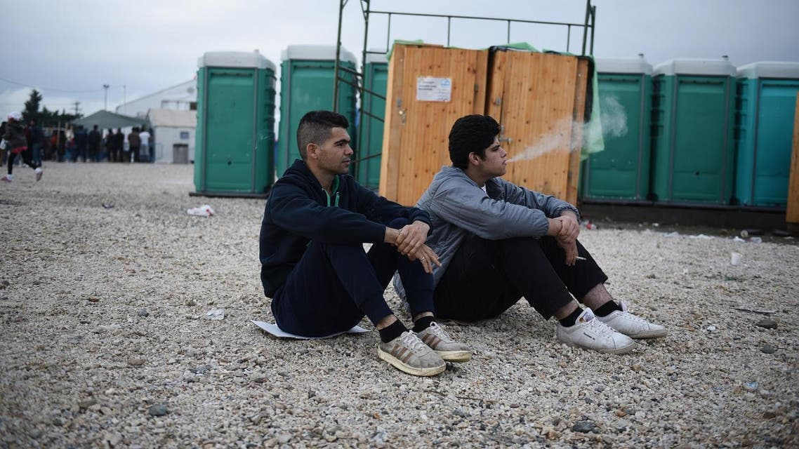 Refugees smoke at a refugee camp, as they wait to be allowed to pass from northern Greek village of Idomeni, to southern Macedonia. (AP)