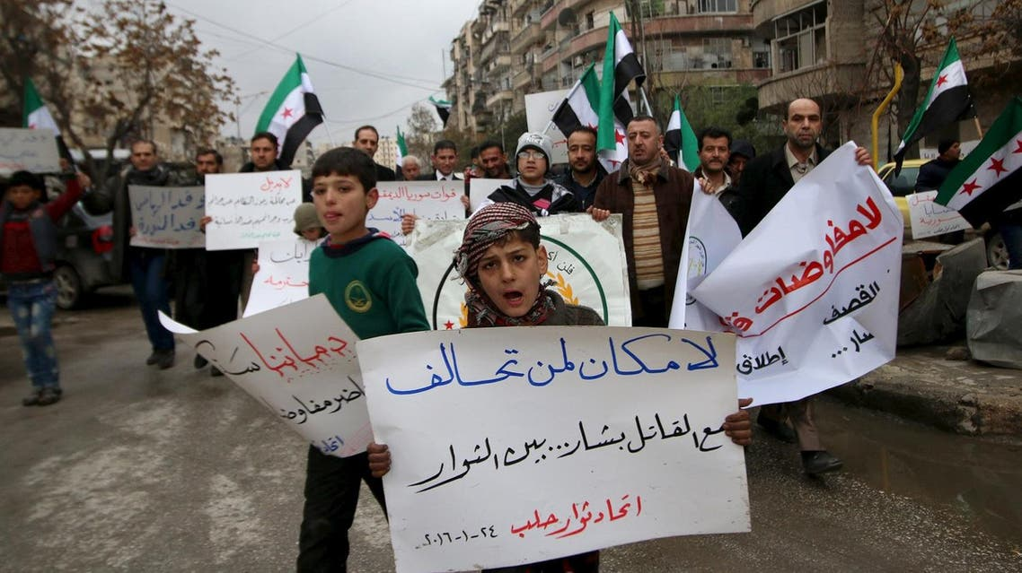 Residents carry banners and opposition flags as they march during a protest in Aleppo, asking for the release of prisoners held in government jails and lifting of the siege on besieged areas. (Reuters)