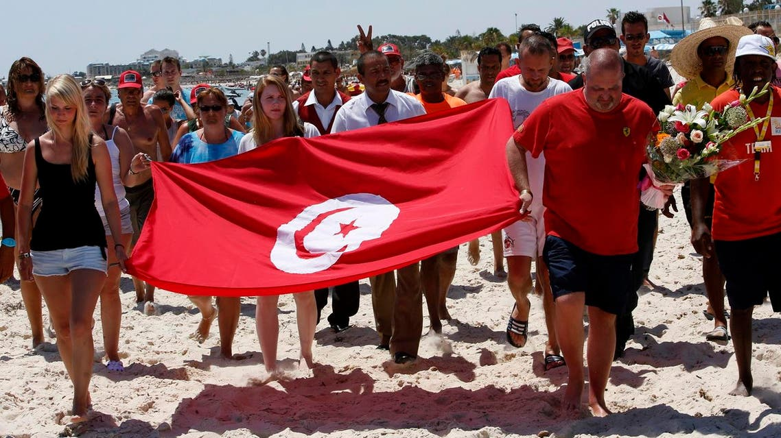 Tourists and residents, some displaying a Tunisian flag, walk on the beach to the scene of the attack in Sousse, Tunisia. (AP)