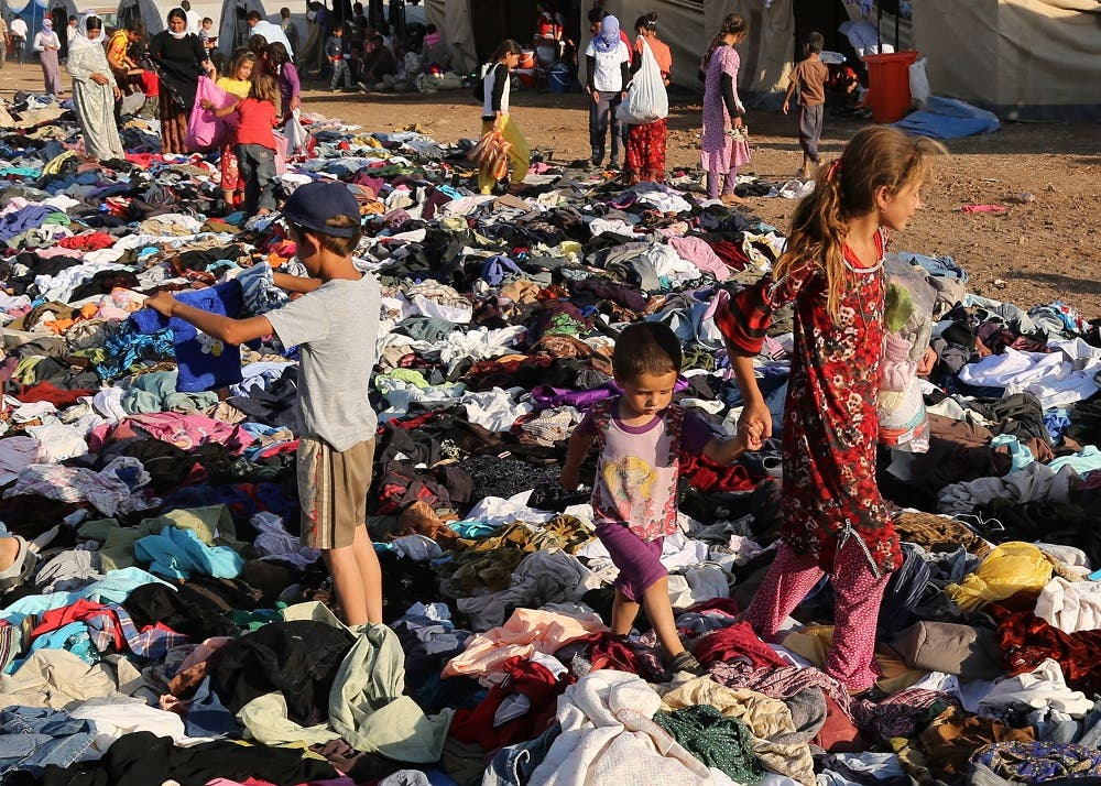 Displaced Iraqis from the Yazidi community look for clothes to wear among items provided by a charity organization at the Nowruz camp, in Derike, Syria, Tuesday, Aug. 12, 2014. In the camps here, Iraqi refugees have new heroes: Syrian Kurdish fighters who battled militants to carve an escape route to tens of thousands trapped on a mountaintop. While the U.S. and Iraqi militaries dropped food and water to the starving members of Iraq's Yazidi minority, the Kurds took it on themselves to rescue them, a sign of how Syria's Kurds, like Iraq's, are using the region's conflicts to establish their own rule. (AP Photo/ Khalid Mohammed)