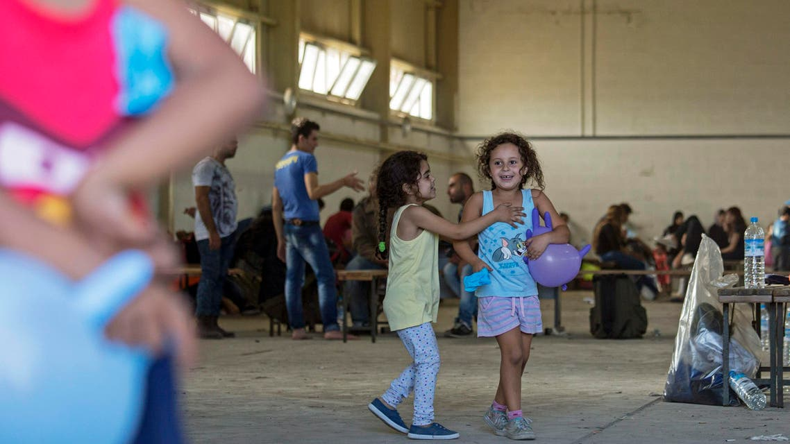 Syrian migrants are temporarily housed at a warehouse after coming ashore at RAF base Akrotiri, Cyprus, Wednesday, Oct. 21, 2015. AP