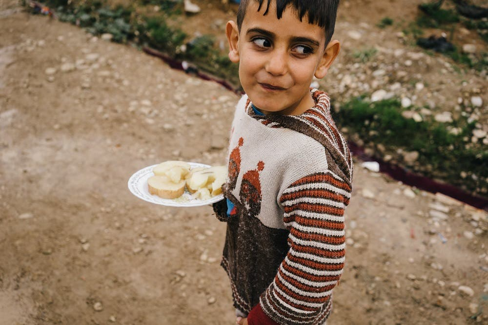 In this Sunday, Jan. 24, 2016 photo, a Syrian boy walks in Kawergosk refugee camp in northern Iraq carrying a plate with boiled potatoes. According to the U.N. children's agency, malnutrition is a major threat among millions of refugees, as people eat less to conserve the little food they do have. (AP Photo/Alice Martins)