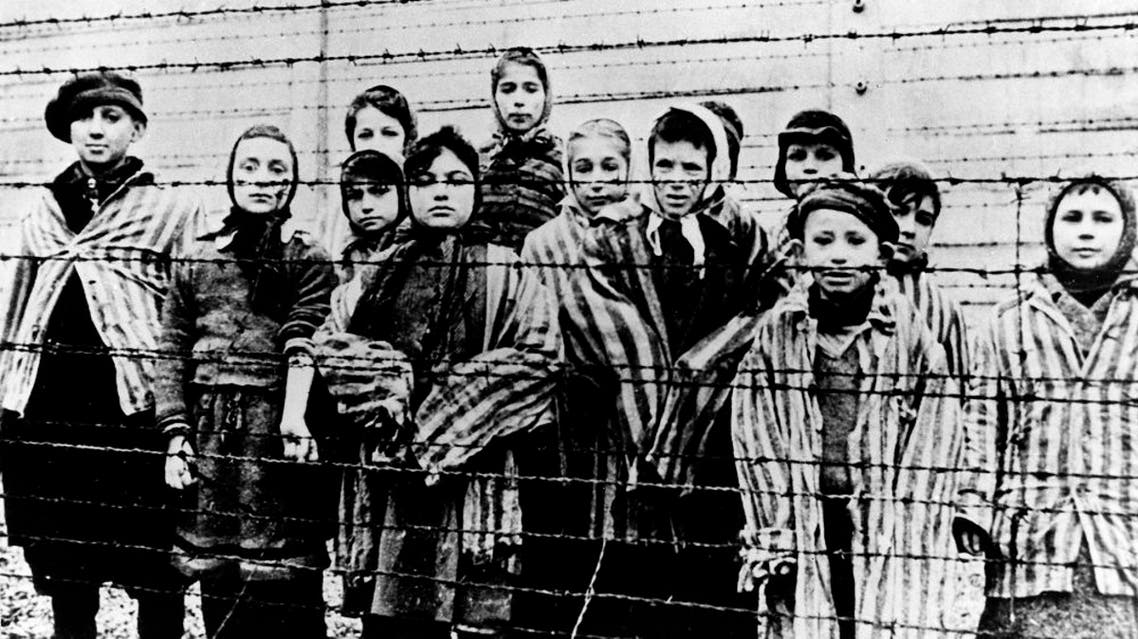 """A picture taken just after the liberation by the Soviet army in January, 1945, shows a group of children wearing concentration camp uniforms behind barbed wire fencing in the Auschwitz Nazi concentration camp. On Thursday Jan. 22, 2015, Russia accused Poland of engaging in a """"mockery of history"""" after the Polish foreign minister Grzegorz Schetyna credited Ukrainian soldiers, rather than the Soviet Red Army, with liberating Auschwitz 70-years ago. The latest exchange comes prior to the 70th anniversary of the liberation of Auschwitz by Soviet troops on Jan. 27, 1945, underlining deep tensions between Russia and Poland, which is hugely critical of Russia's recent actions in Ukraine. (AP Photo/FILE)"""
