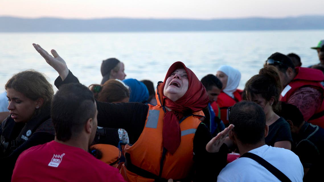 A woman reacts as she arrives aboard a dinghy after crossing from Turkey, to the island of Lesbos, Greece, on Saturday, Sept. 19, 2015. AP
