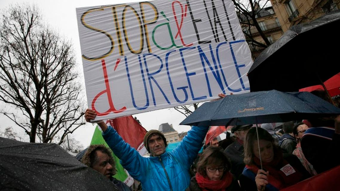 """A protester holds a banner reading: """" Stop of state of emergency"""" during a protest, in Paris, Saturday, Jan. 30, 2016. France imposed a state of emergency, which gives more power to police and administrative authorities, after the Nov. 13 Paris attacks that killed 130. Last week, a French high court upheld the measure, saying the danger """"has not disappeared."""" (AP Photo/Christophe Ena)"""