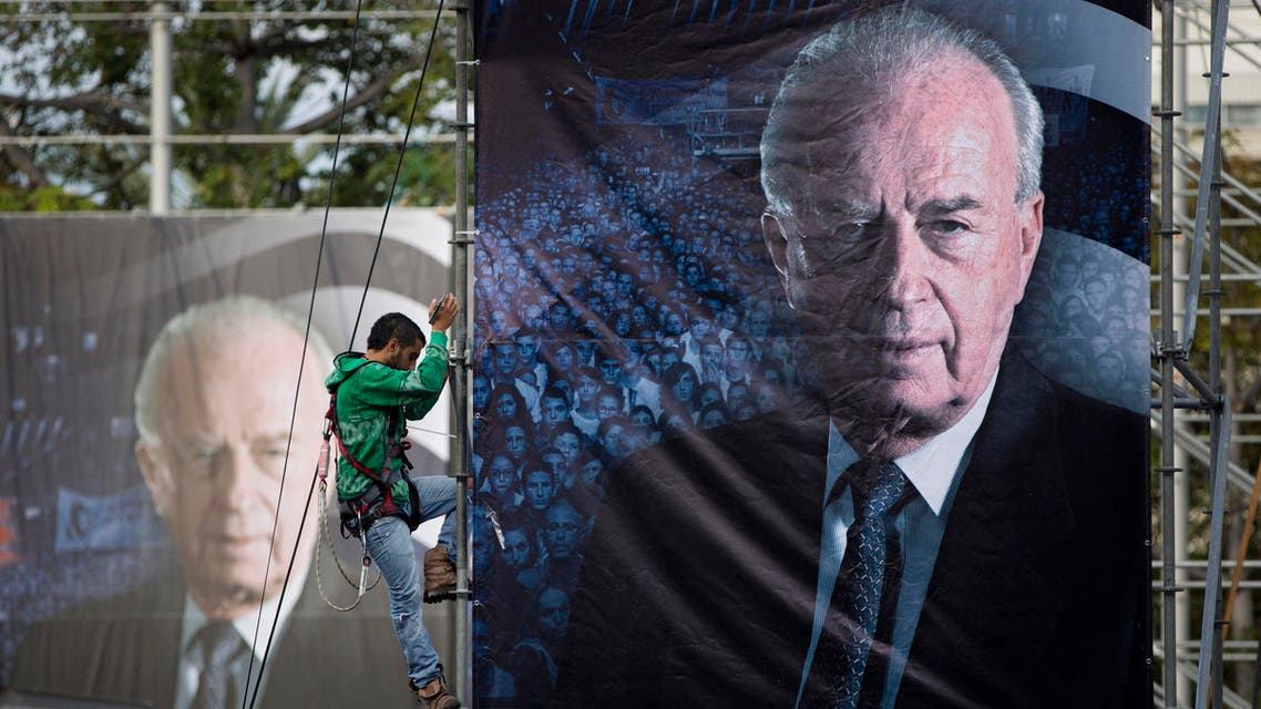 An Israeli worker hangs up a billboard with a portrait of late Israeli Prime Minister Yitzhak Rabin, ahead of a memorial rally for the 20th anniversary of his assassination at Rabin square in Tel Aviv, Israel, Friday, Oct. 30, 2015. AP