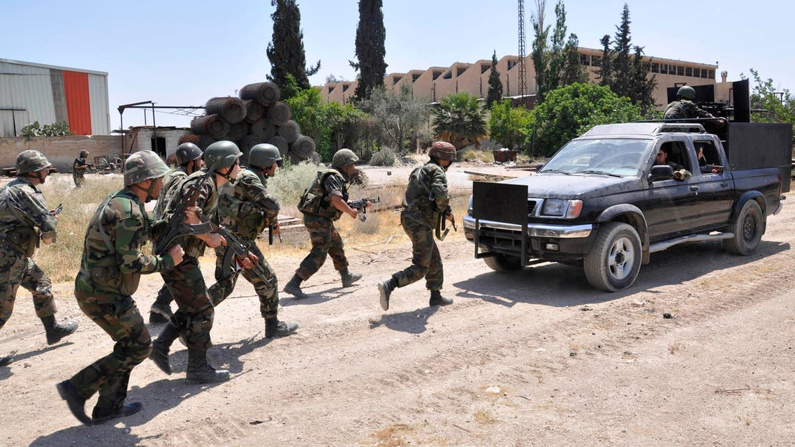 In this file photo released on Sunday, May 26, 2013, by the Syrian official news agency SANA, Syrian forces loyal to Syrian President Bashar Assad take their position during clashes against Syrian rebels, in Aleppo, Syria.