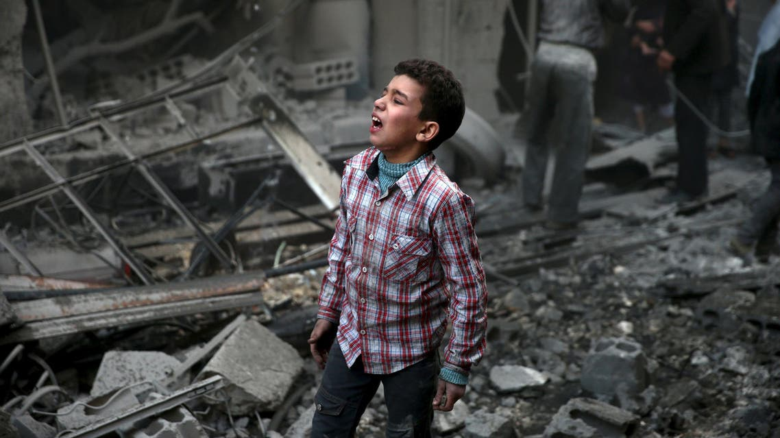 A boy reacts in a site hit by what activists said were airstrikes carried out by the Russian air force in the town of Douma, eastern Ghouta in Damascus, Syria January 10, 2016. reuters