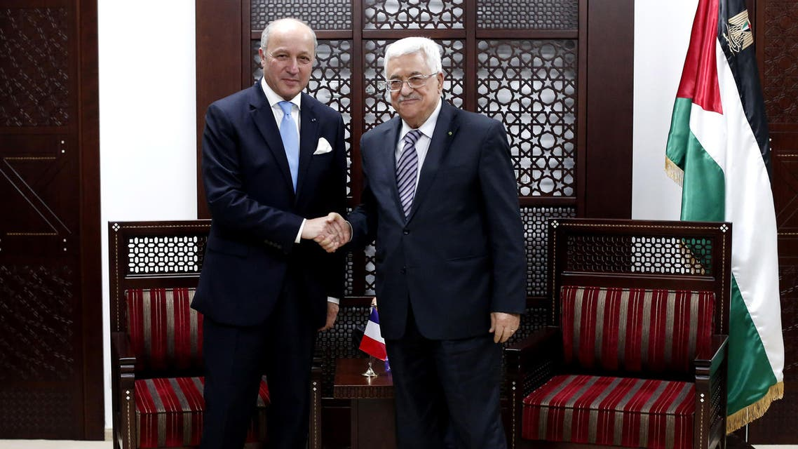 French Foreign Minister Laurent Fabius, left, shakes hands with Palestinian President Mahmoud Abbas for a photograph, in the West Bank city of Ramallah, Sunday, June 21, 2015. (AP)
