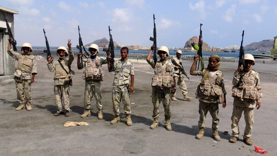 Army soldiers hold up their weapons after taking over the main port of Yemen's southern city of Aden from gun men, January 4, 2016