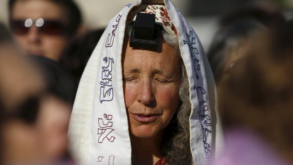 """A member of """"Women of the Wall"""" group wears a Jewish prayer shawl and Tefillin, leather straps and boxes containing sacred parchments, that Orthodox law says only men should don, during a monthly prayer session at the Western Wall in Jerusalem's Old City, in this May 10, 2013 file photo. The Israeli government approved on January 31, 2016 the creation of a mixed-sex plaza near Jerusalem's Western Wall to accommodate Jews who contest Orthodox curbs on worship by women at the site. REUTERS/Amir Cohen/Files"""
