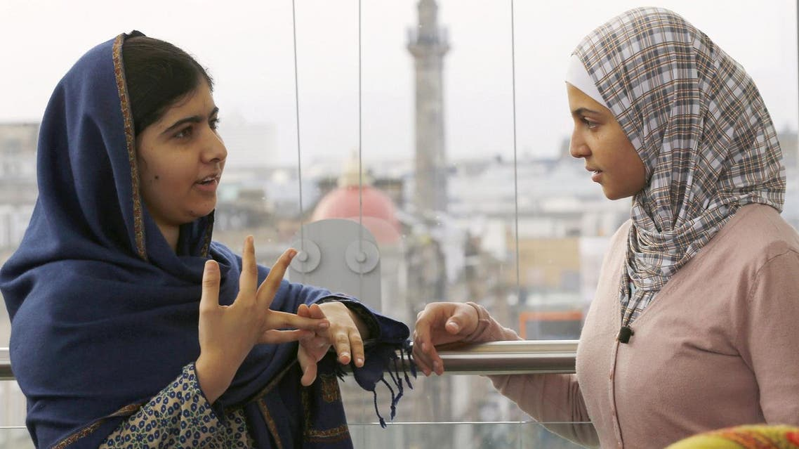 Malala Yousafzai (L) and Syrian refugee Muzoon Almellehan, 17, speak at the City Library in Newcastle upon Tyne, Britain, in this December 22, 2015 file picture.