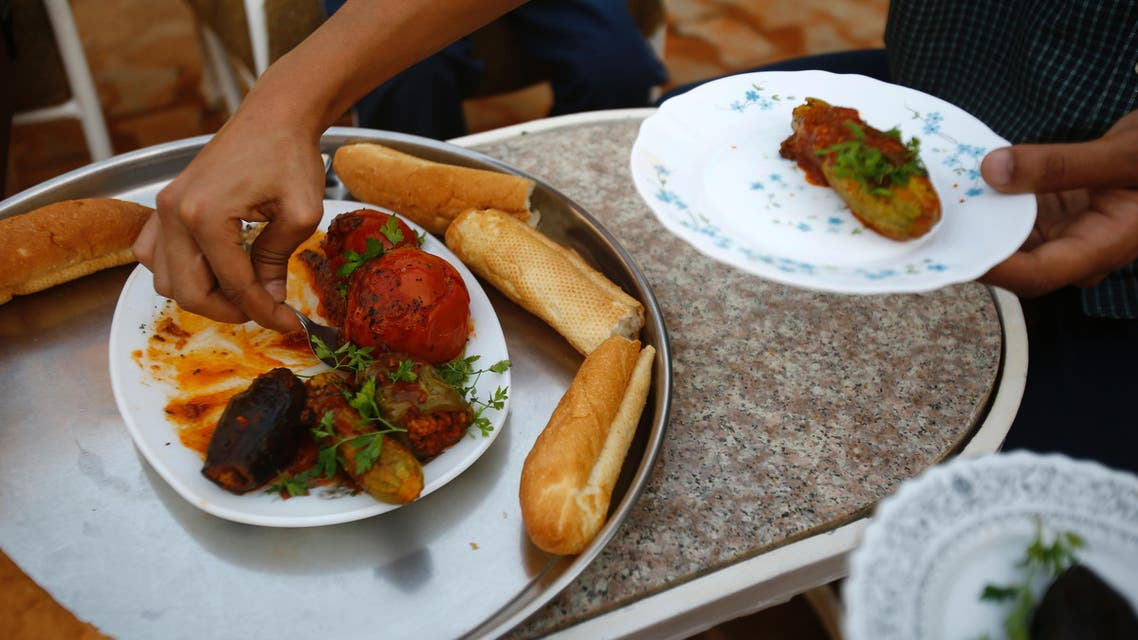 "Omer Eltigani, a young British Sudanese pharmacist, serves Sudanese ""Mahshi"" (stuffed vegetables) that he prepared on January 11, 2016 at his aunt's house in Khartoum."