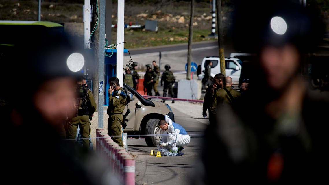 Israeli security forces inspect the site next to the body of a Palestinian identified as Amjad Sukkari, at the checkpoint between the city of Ramallah and Jewish settlement of Beit El in the West Bank, Sunday, Jan. 31, 2016. AP