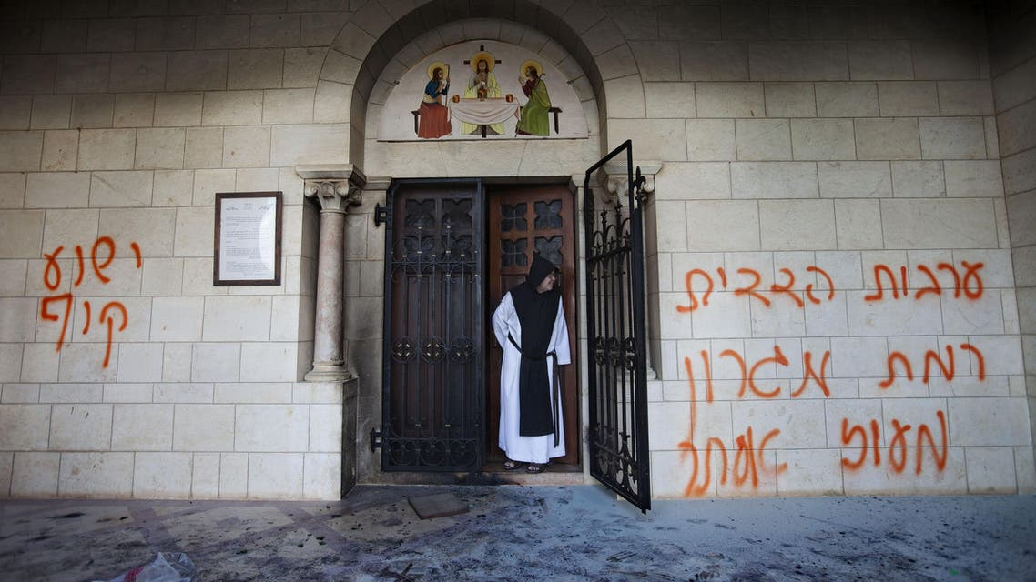 A catholic monk stands in a doorway of the Latrun Trappist Monastery where Israeli police say vandals overnight have spray-painted anti-Christian and pro-settler graffiti and set the monastery's door on fire, in Latrun, between Jerusalem and Tel Aviv, Israel, Tuesday, Sept 4, 2012.
