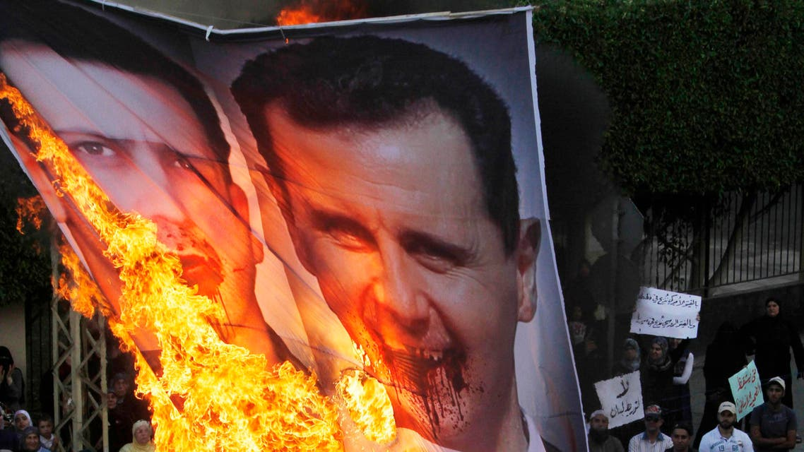 Protesters chant slogans against the Syrian regime and Russia's support of President Bashar Assad as they burn a banner depicting Assad, top, his brother, Maher Assad and Russian President Vladimir Putin, bottom, in the southern port city of Sidon, in Lebanon, Sunday, June 17, 2012. (AP Photo/Mohammed Zaatari)