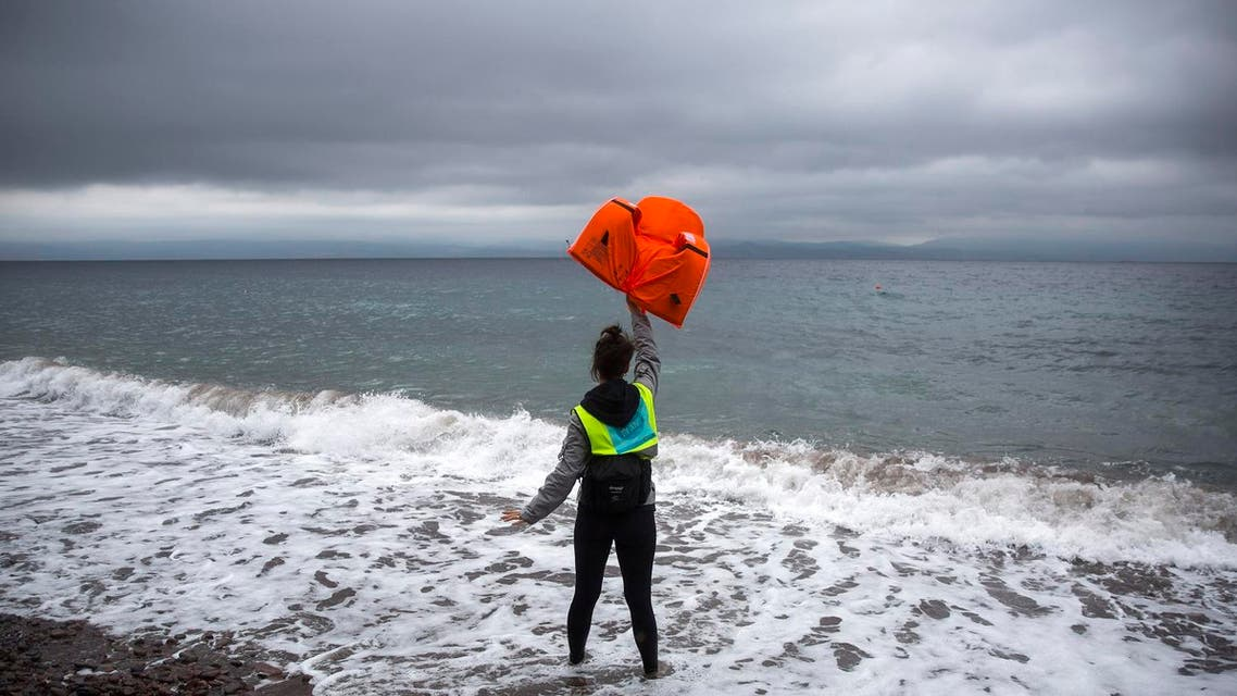 A volunteer holds up a lifejacket as migrants and refugees approach on a dinghy the northeastern Greek island of Lesbos from the Turkish coast, Thursday, Oct. 22, 2015.