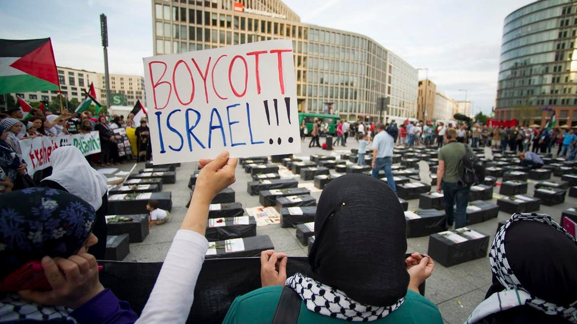 """A woman holds a sign which reads """"Boycott Israel"""" in front of symbolic coffins while attending a demonstration supporting Palestine, in Berlin. (File photo: Reuters)"""